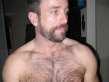 Topless dude showing off his hairy chest and flexing muscles