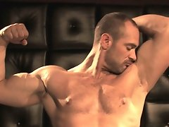Craig Reynolds is standing on a lighted platform flexing his substantial muscles. He poses, flexing his giant chest, massive arms and meaty legs. He t