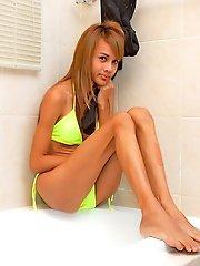 Leggy shemale peels off her robe and bright bikini