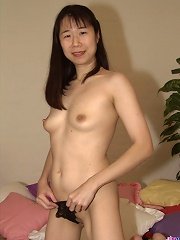 Mature asian wife spreads and fingers her hairy pussy on bed